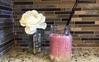 Smoothie in glass and white flower in vase