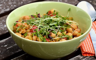 green bowl with chickpea salad and sprouts on grayish outdoor table